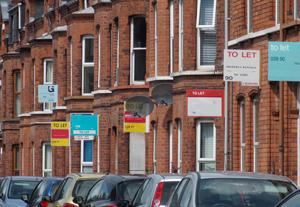 """Photo of terraced houses with """"to let"""" signs attached"""